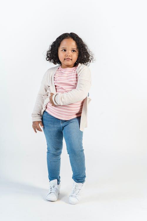 Cute black girl in casual outfit in studio