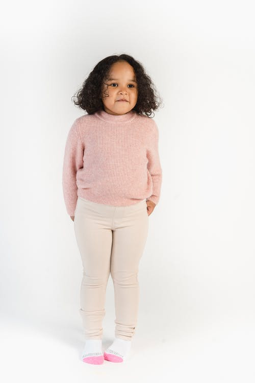 Cute black girl in sweater and skinny pants in studio
