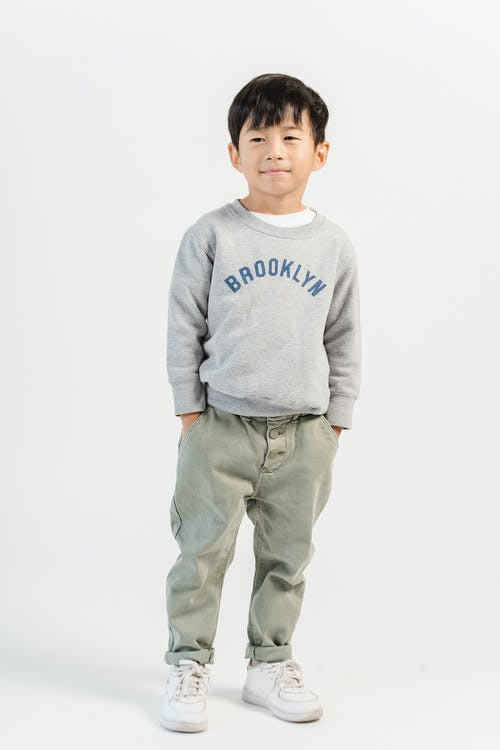 Full body of adorable Asian boy with hands on pockets wearing casual jeans and sweatshirt with sneakers in white studio