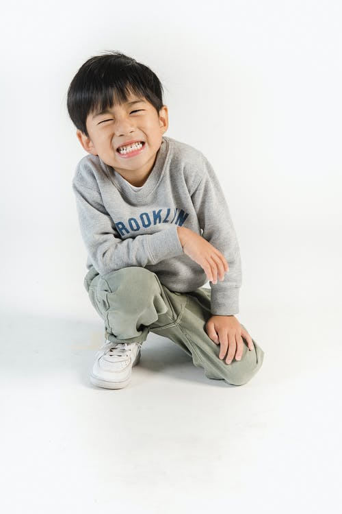 Full body of positive Asian kid wearing trendy clothes showing toothy smile in white studio
