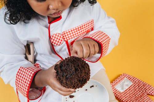 Crop little black chef with muffin on yellow background