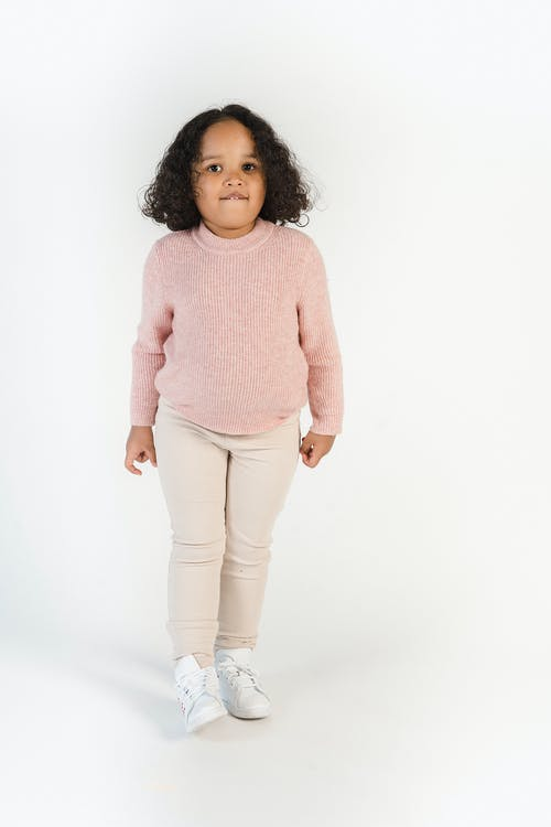 Charming Hispanic girl in trendy wear on white background