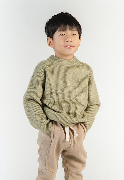 Dreamy Asian boy in stylish wear on white background