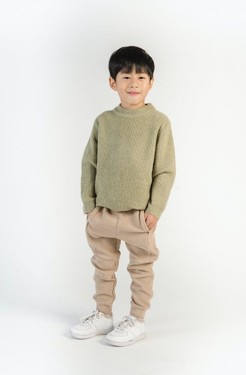 Smiling ethnic boy in trendy outfit on white background