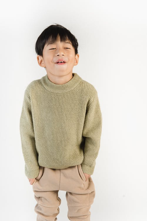 Content Asian boy in trendy wear on white background