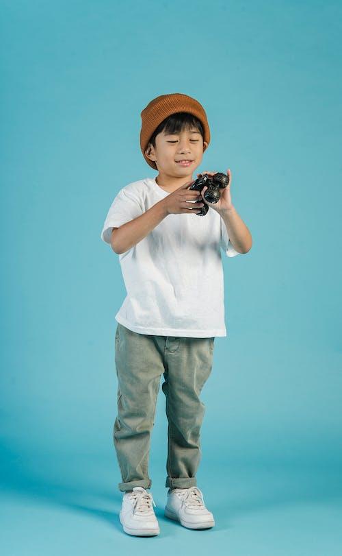 Asian boy in trendy wear with toy car