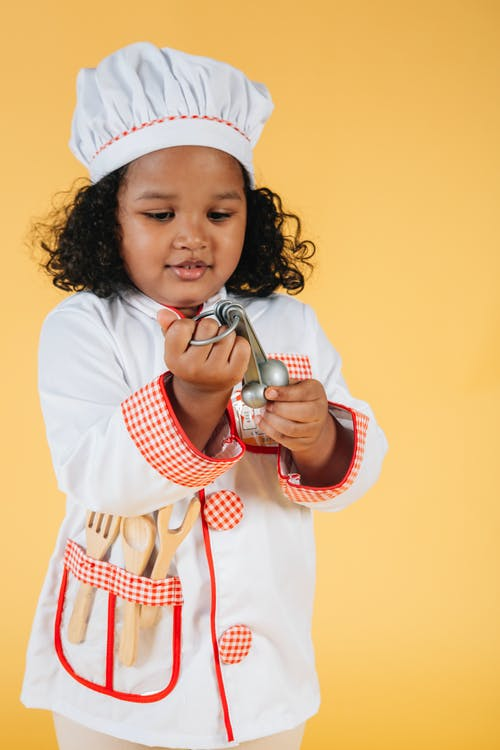 Cute black girl in costume of cook looking at spoons