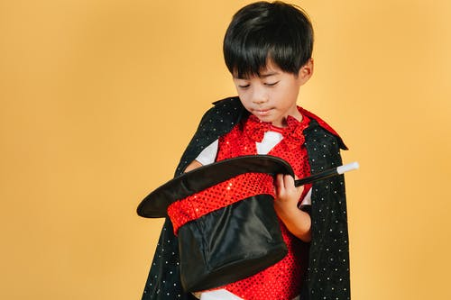 Little Asian boy in costume of magician
