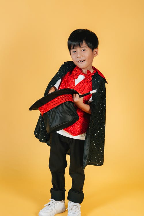 Cute funny Asian boy in costume of magician
