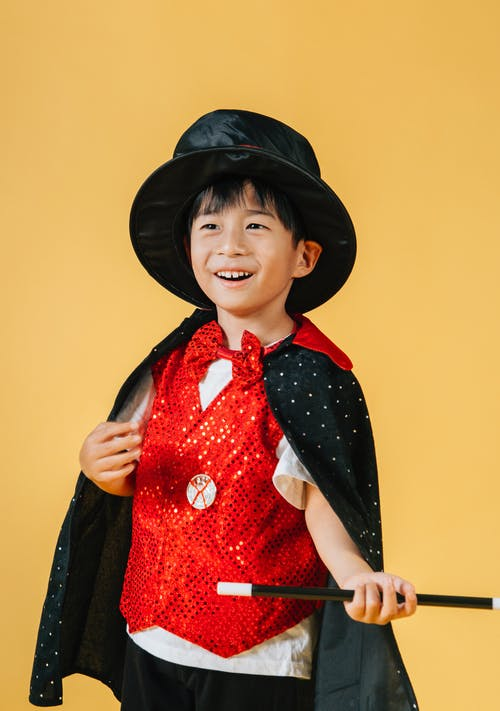 Cheerful Asian boy in costume of magician with magic wand