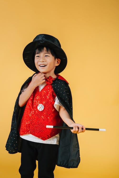 Cheerful Asian boy with magic wand pretending magician in costume