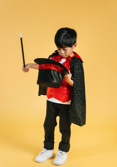 Full body of adorable magician Asian boy wearing cape standing on yellow background with wand and looking into black hat in studio