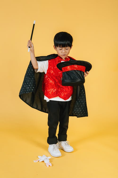 Full body of little ethnic boy in magician costume with cape doing magic trick while using cylinder hat and magic wand while standing on orange background