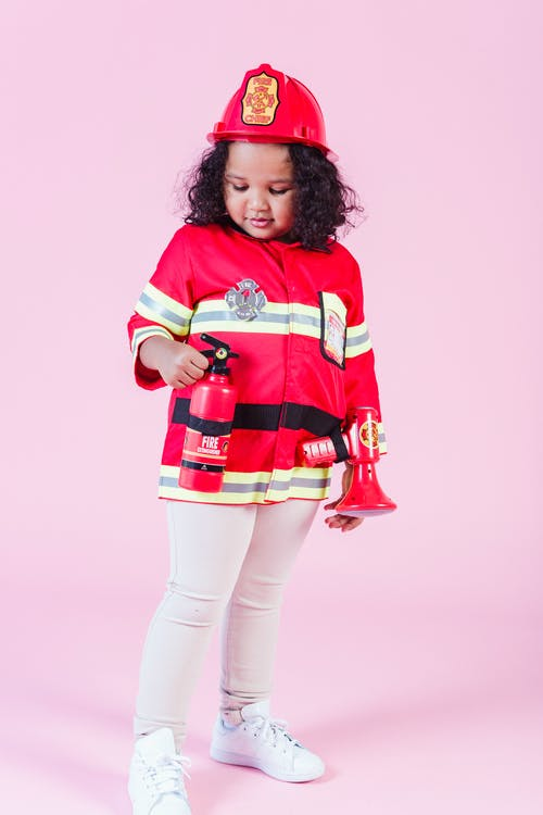 Little ethnic girl in fireman costume in studio