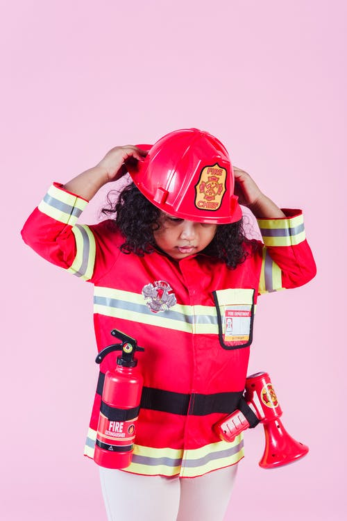 Ethnic child wearing firefighter costume in room