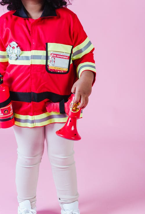Faceless ethnic kid in fireman costume in studio