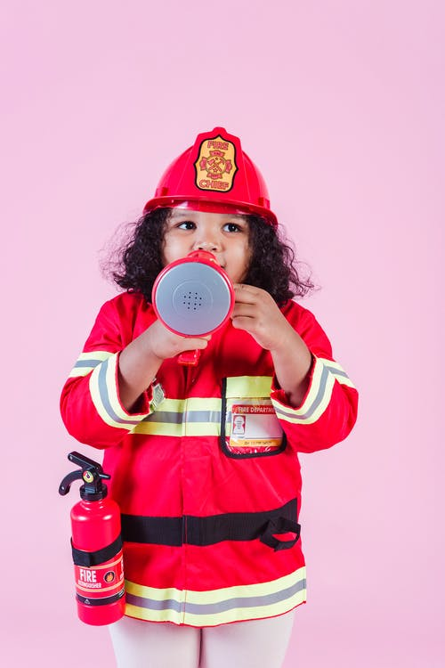 Ethnic girl wearing firefighter costume using megaphone