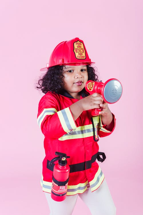Little ethnic girl in fireman costume using loudspeaker