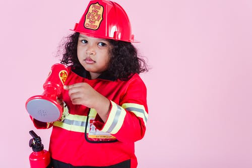 Ethnic girl in firefighter costume in studio