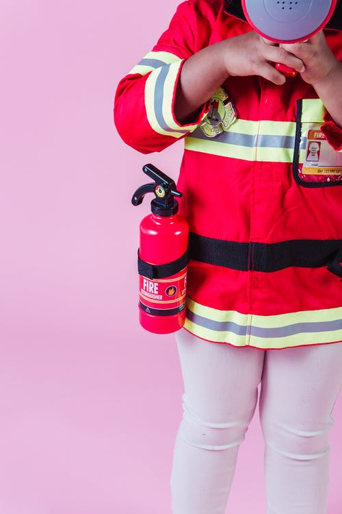 Crop faceless little ethnic child in firefighter costume and fire extinguisher with fake megaphone and standing on pink background