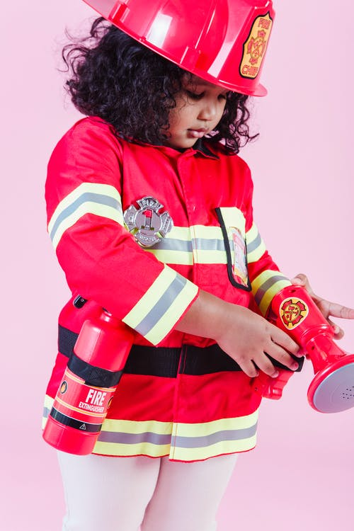 Little ethnic girl wearing fireman costume and using fake loudspeaker