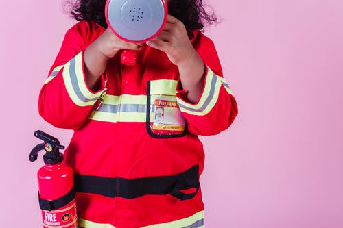 Crop unrecognizable little ethnic kid wearing fireman costume and fire extinguisher while using loudspeaker toy and standing on pink background