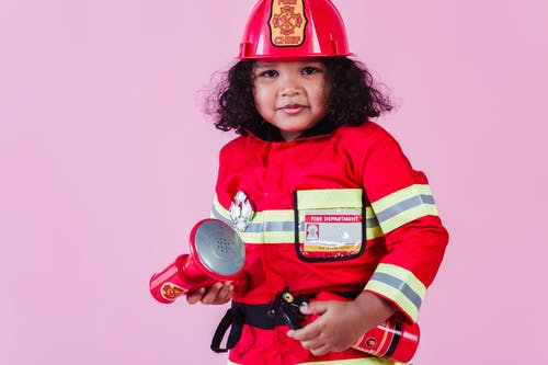 Ethnic girl in firefighter costume with fake megaphone