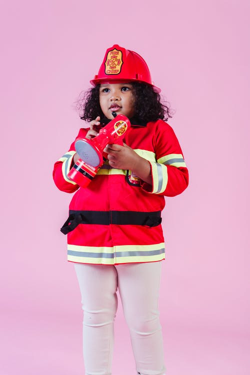 Ethnic kid wearing fireman costume using loudspeaker toy