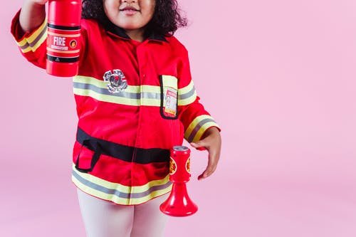 Crop anonymous little ethnic kid in fireman costume with fake fire extinguisher and megaphone standing on pink background