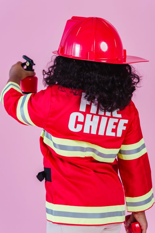 Back view of crop faceless little ethnic child in firefighter costume and helmet demonstrating fake fire extinguisher while standing on pink background