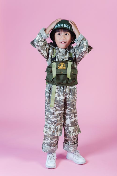 Little Asian boy in navy uniform in studio