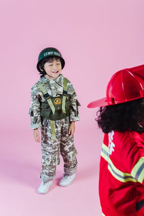 Multiracial children in military outfit and fireman costume in studio