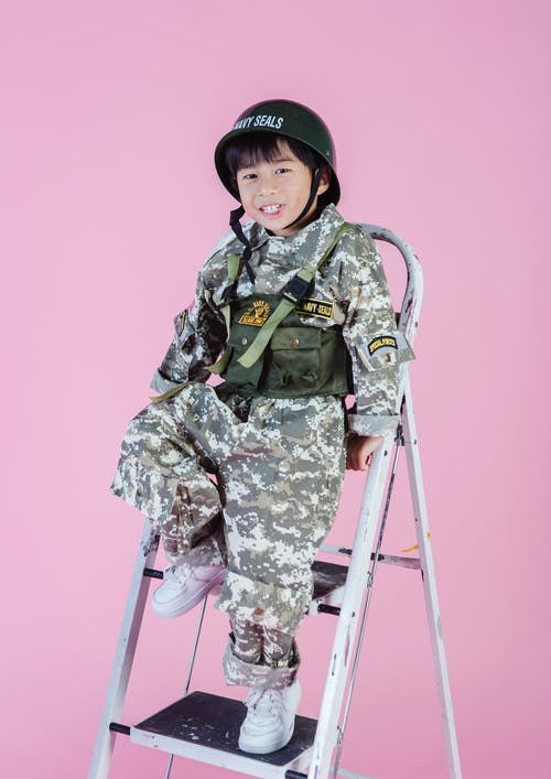 Smiling little Asian boy in navy uniform on ladder