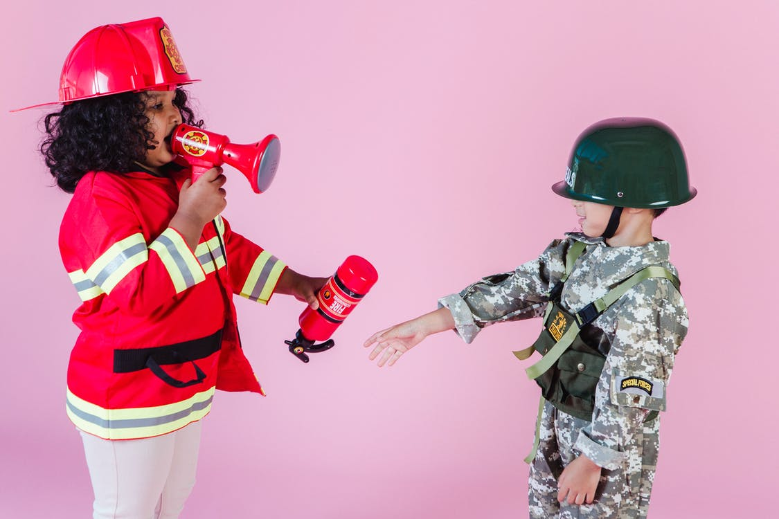 Side view of multiracial children in military uniform and fireman costume with megaphone and fire extinguisher standing together on pink background in helmets