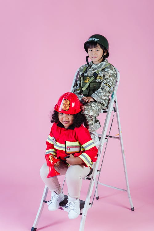 Multiethnic kids wearing navy costume and firefighter costume in studio