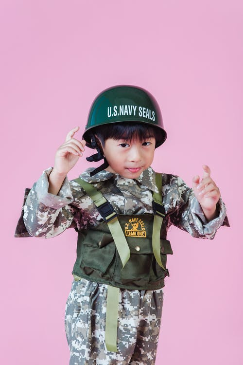 Little Asian kid in navy uniform in studio