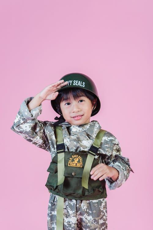 Niño Con Uniforme De Camuflaje Verde Vistiendo Gorra Negra Y Roja