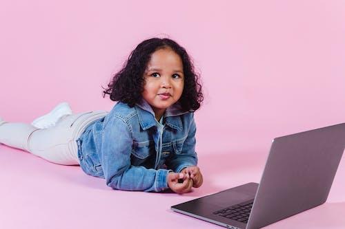 Chica En Chaqueta De Mezclilla Azul Y Pantalón Blanco Sentado En El Suelo Con Macbook