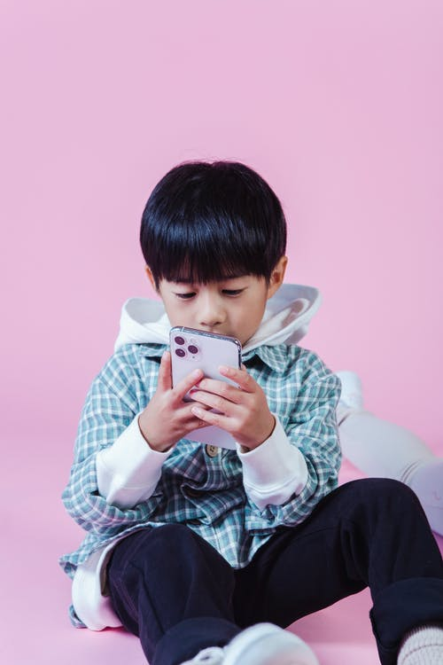Little Asian kid in casual outfit sitting on floor and using smartphone on pink background