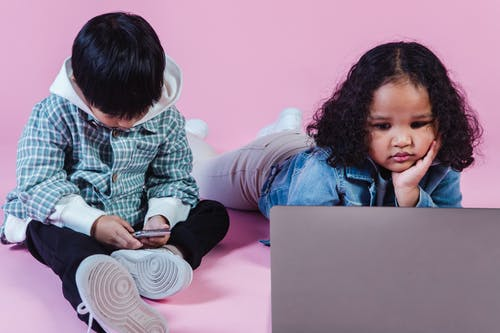 Multiracial children with laptop and phone in studio
