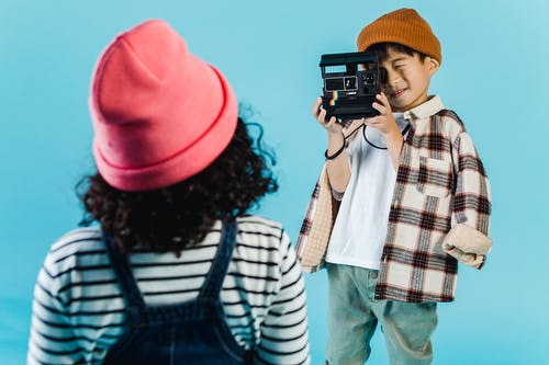 Multiethnic kids in casual outfit and hats using retro camera while standing on blue background in room
