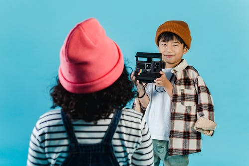 Multiethnic kids in trendy outfits and hats standing on blue background and using retro camera while taking photo