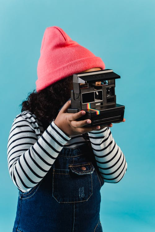 Anonymous ethnic little girl with curly hair in casual clothes taking pictures on instant photo camera against blue background