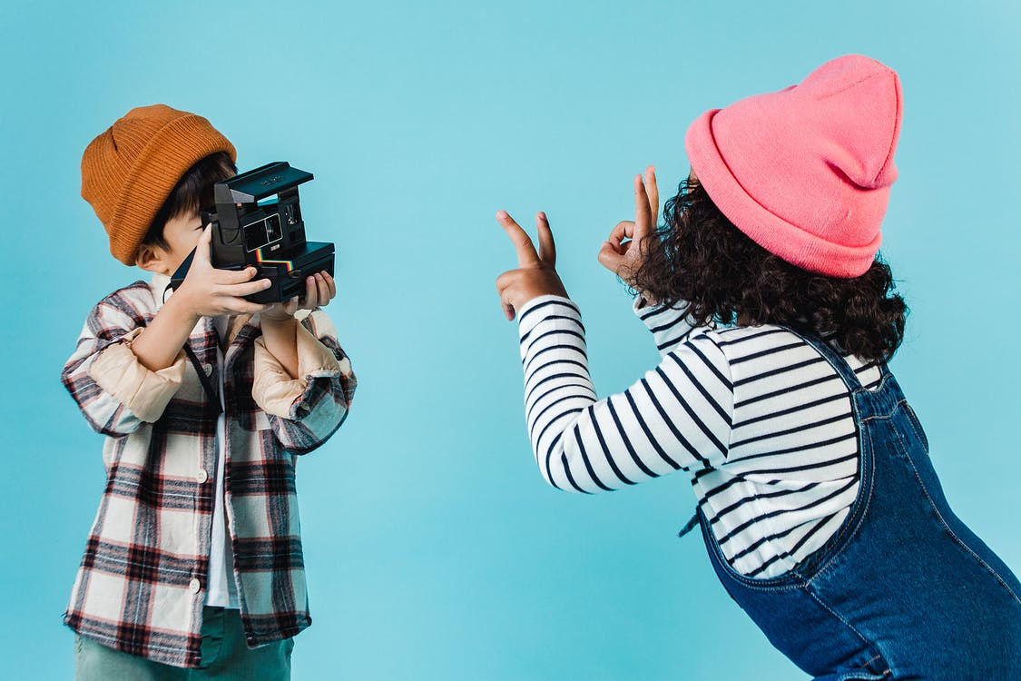 Positive diverse children taking photo on instant photo camera