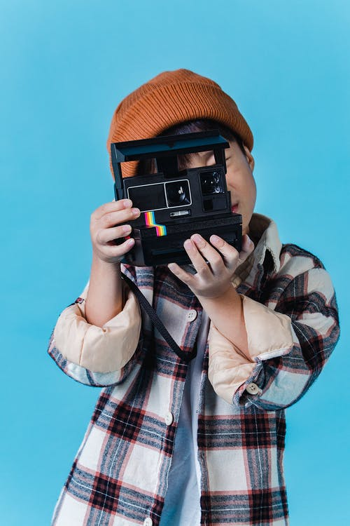Anonymous Asian boy in stylish clothes standing in studio with blue walls and taking photo on instant photo camera