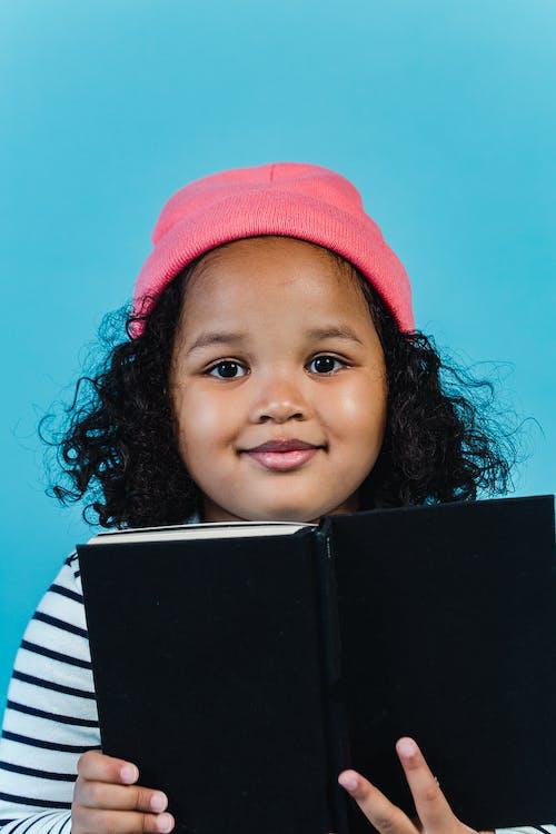 Positive black girl reading book against blue  background