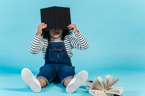 Unrecognizable little African American girl in trendy clothes sitting on floor with textbooks and covering face with book against blue background