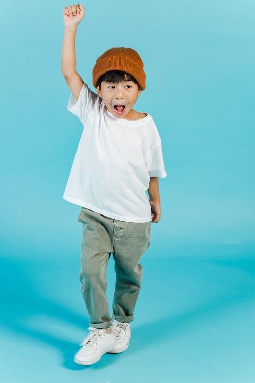 Junge Im Weißen Rundhalsausschnitt T Shirt Und In Den Grauen Hosen, Die Stehen Und Seine Rechte Hand Heben