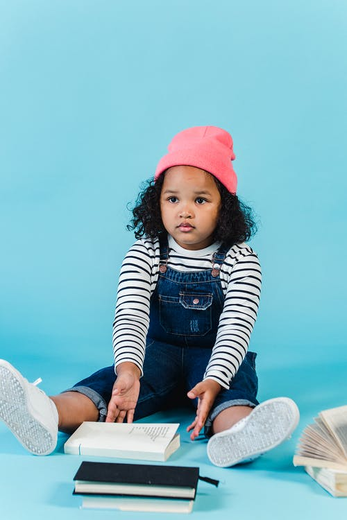 Full body of bewildered African American kid wearing hat and denim overall looking away while sitting on blue background with pile of books