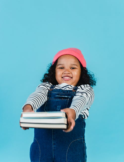 Smiling African American kid wearing hat looking at camera while standing in studio on blue background with books in outstretched arms